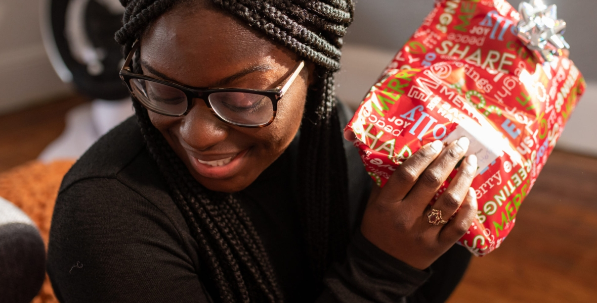 Young woman opening kwanzaa presents.