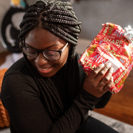 Young woman opening kwanzaa presents.
